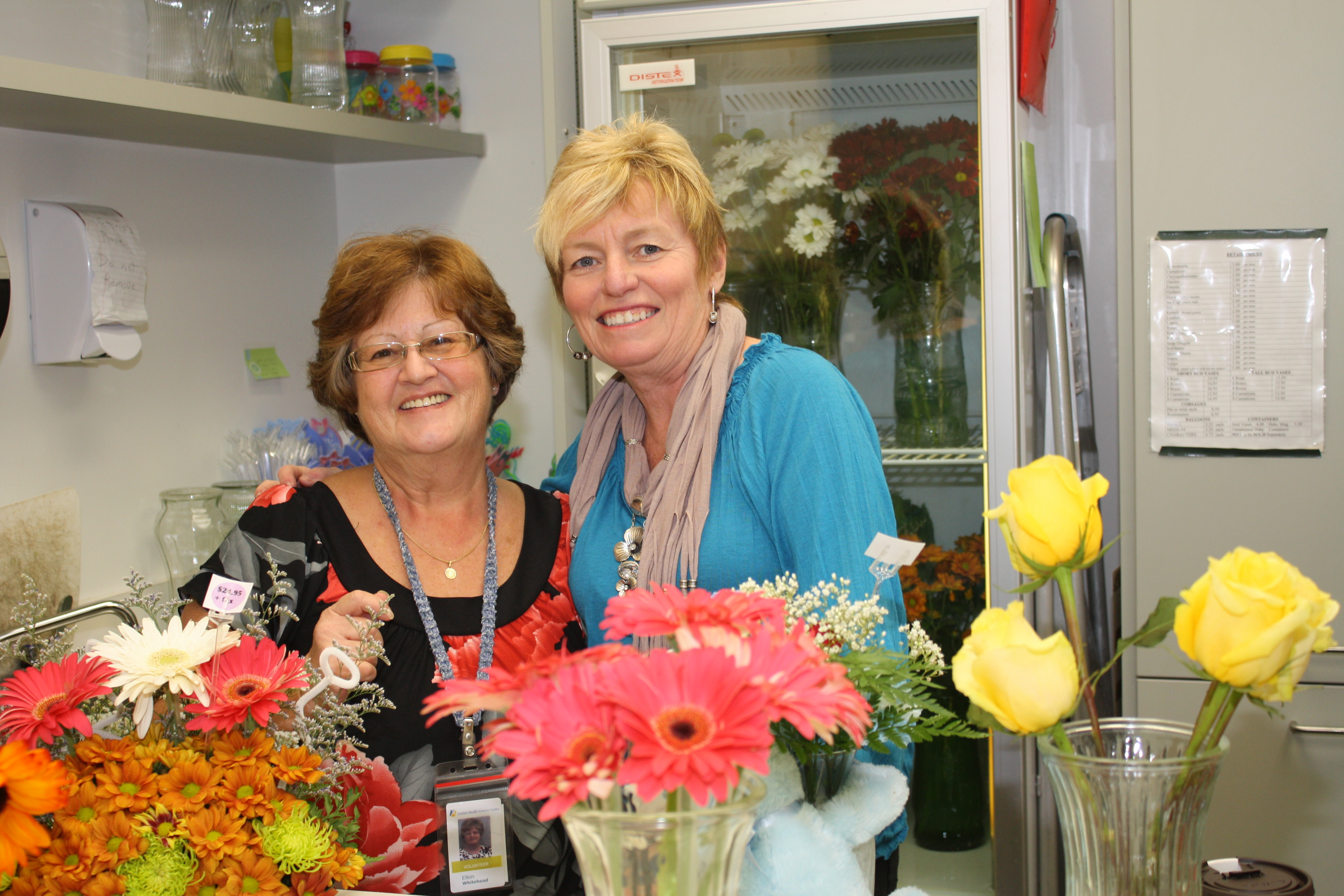 Two smiling auxiliary volunteers behind flower arrangement