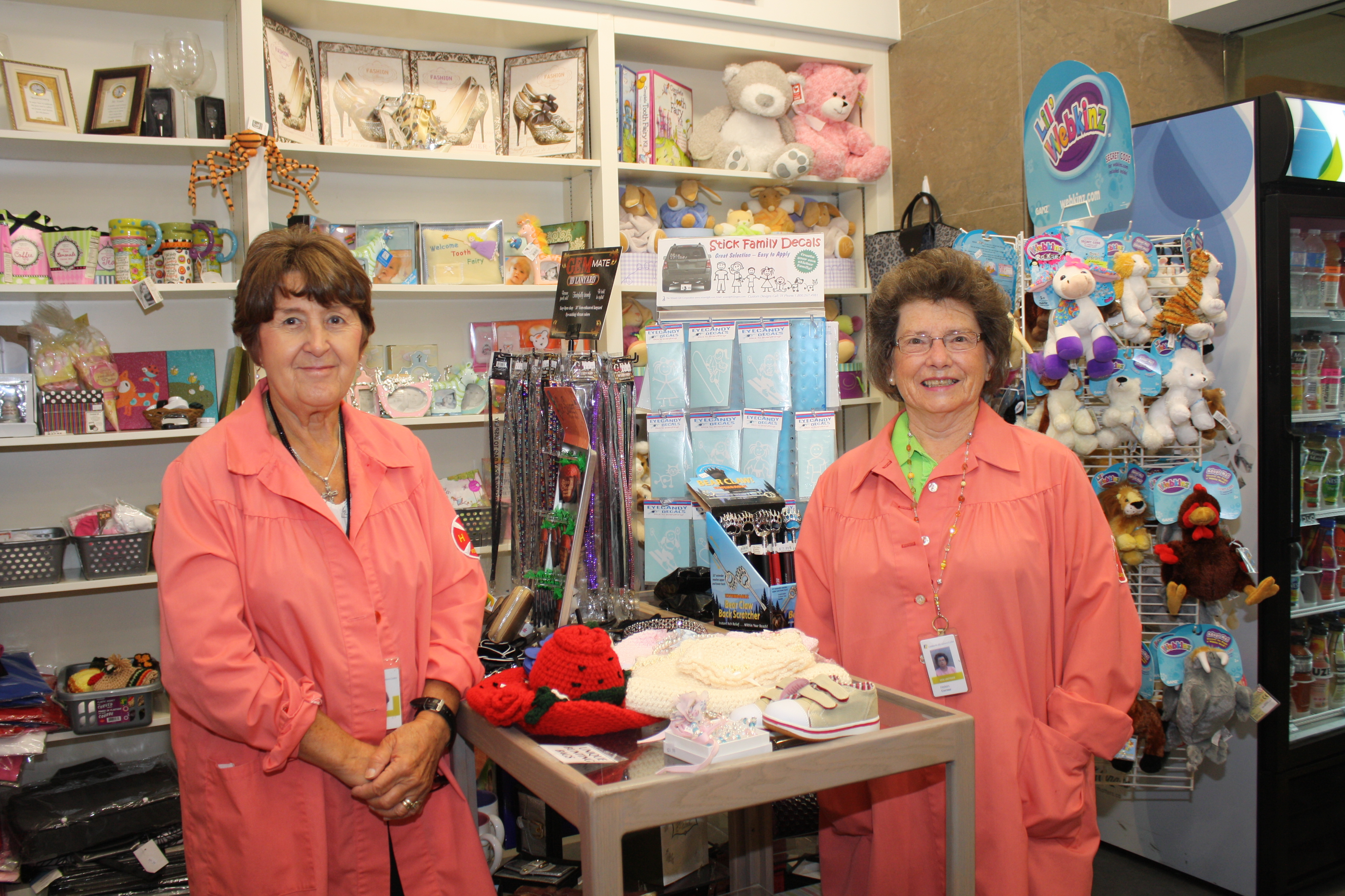Two auxiliary volunteers smile side by side in the gift shop